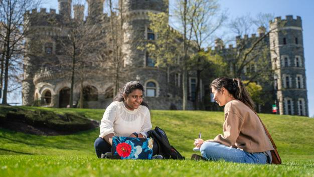 Students sitting on Haber Green with Grey Towers Castle in the background
