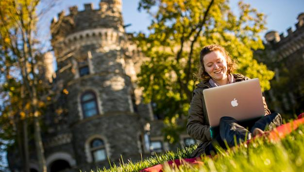 Female Arcadia University student on laptop in front of castle on campus