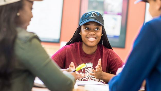 Arcadia student smiling in a group at dining table