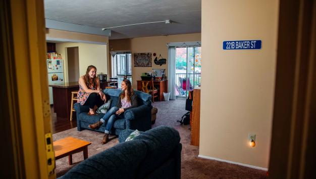 Two female students sit on a couch in Oak Summit apartment complex.