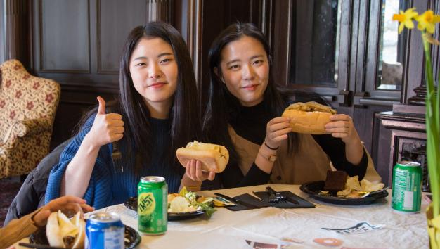 Two Arcadia international students eating lunch and giving a thumbs up