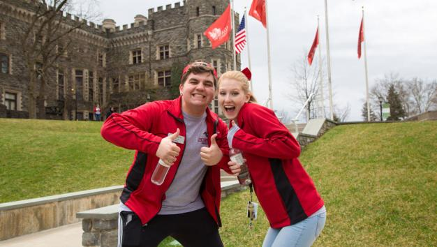 Two Arcadia student ambassadors giving thumbs up in front of grey towers castle