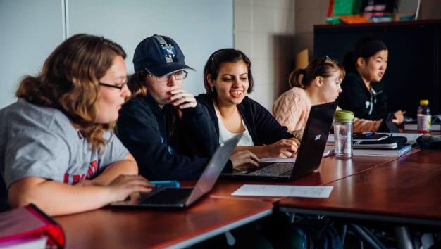 Five female students sit in classroom working on laptops.