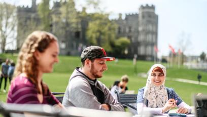 Students at a table outside University Commons with Grey Towers Castle in background