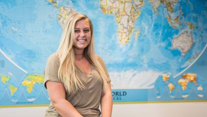 Graduate and Fulbright scholar Heidi Specht sitting in front of Easton Hall map