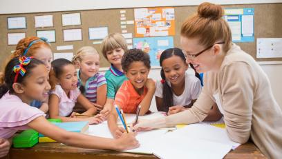 Female educator drawing on paper with young diverse students