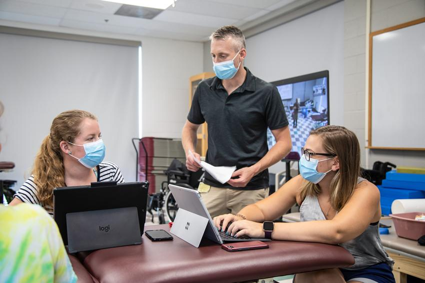 Dr. Michael Tevald works with two female students, all wearing masks.