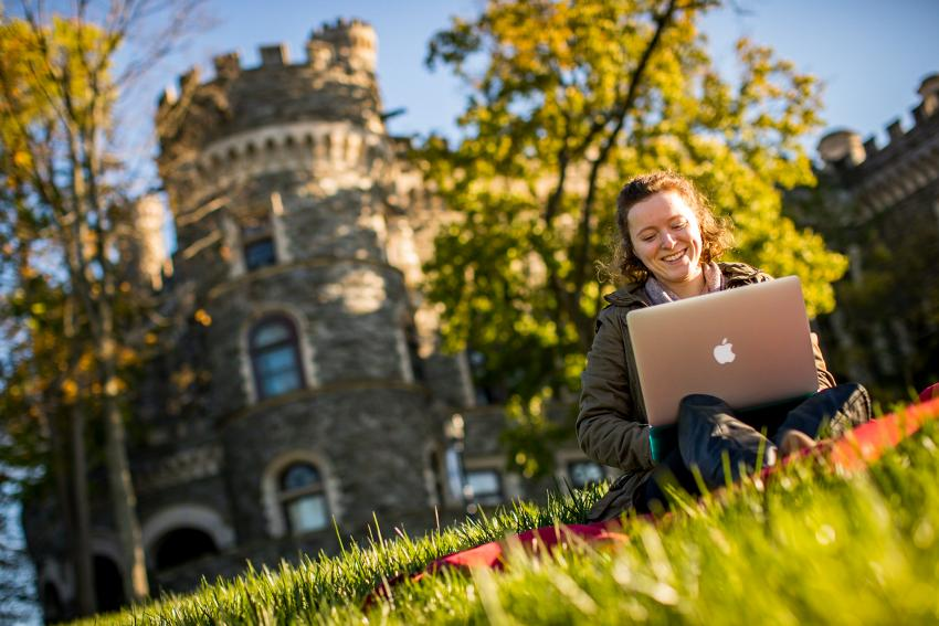 Female arcadia university student on computer in front of grey towers castle