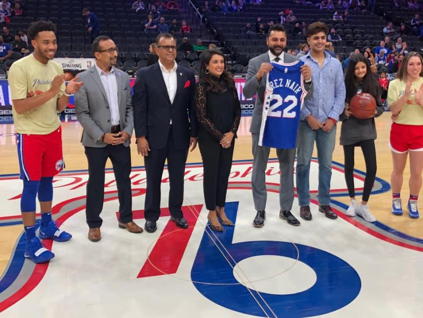 President Nair with the 22 Sixers jersey, surrounded by family