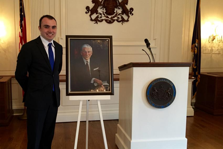 Alex Merker '17 at an award ceremony at the Governor's Mansion, standing with a portrait of James A. Finnegan.