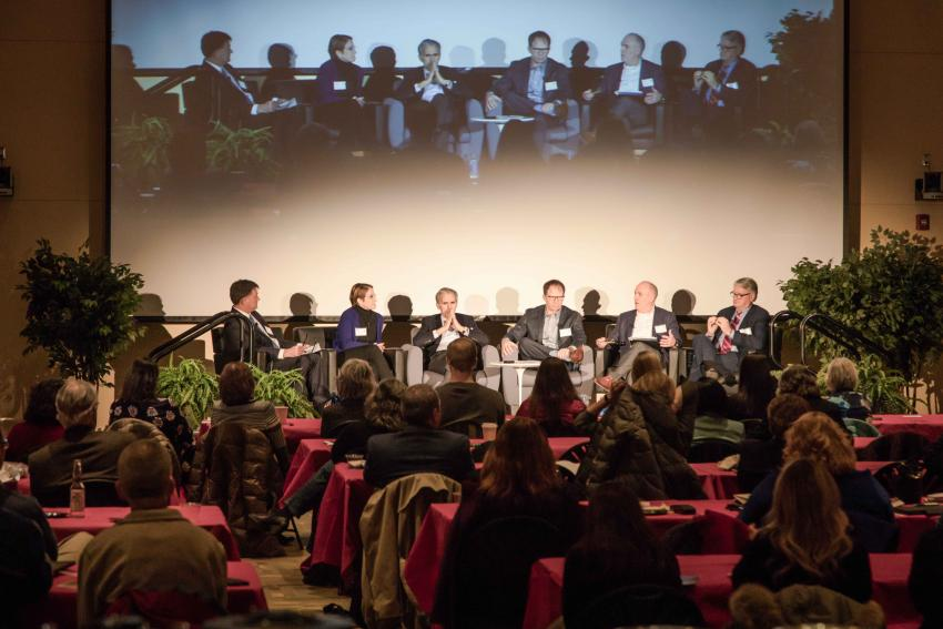 The moderator and 5 panelists on stage with audiences at tables