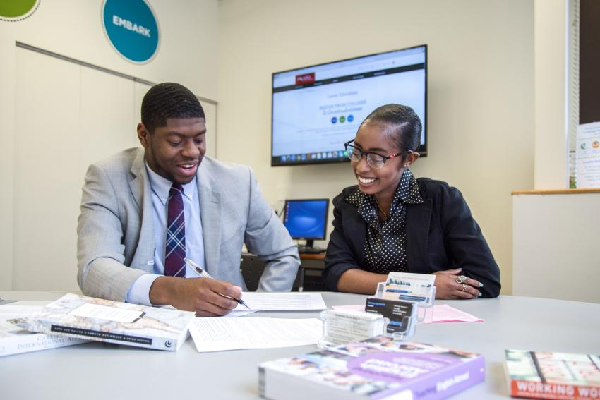 Female career education advisor (right) reviewing paper with male student (left)