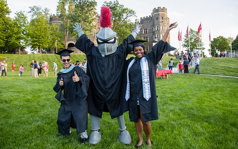 Two students in caps and gowns with the Knight in front of Grey Towers Castle