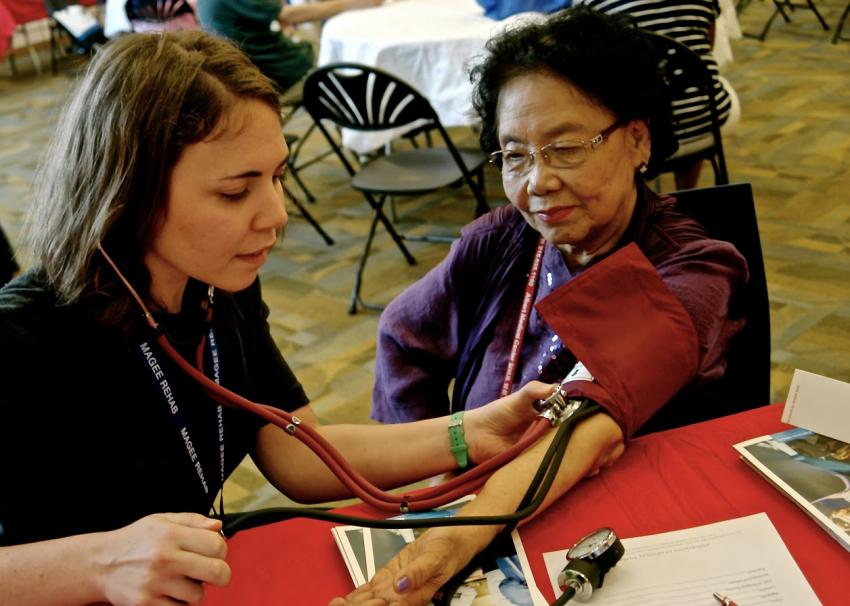<b>Janet Hertz '16DPT</b> takes the blood pressure of an attendee at the Korean Health Expo.