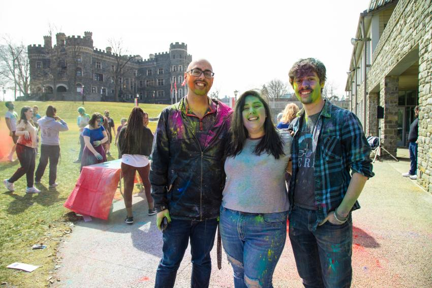 Three students with powdered color paint splashed on them in front of castle