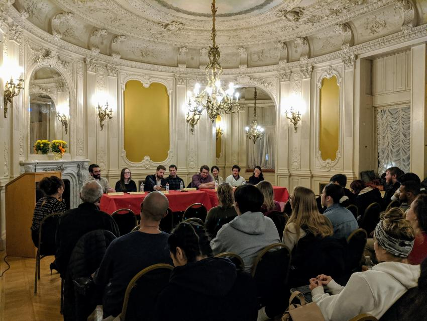 Panelists in the rose room of the castle with an audience