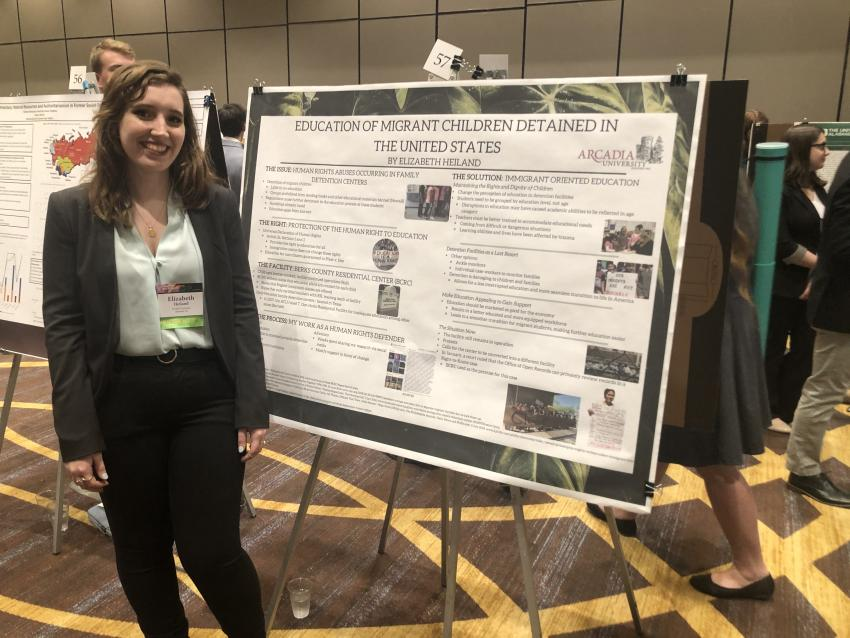 Elizabeth Heiland with her poster at the conference.