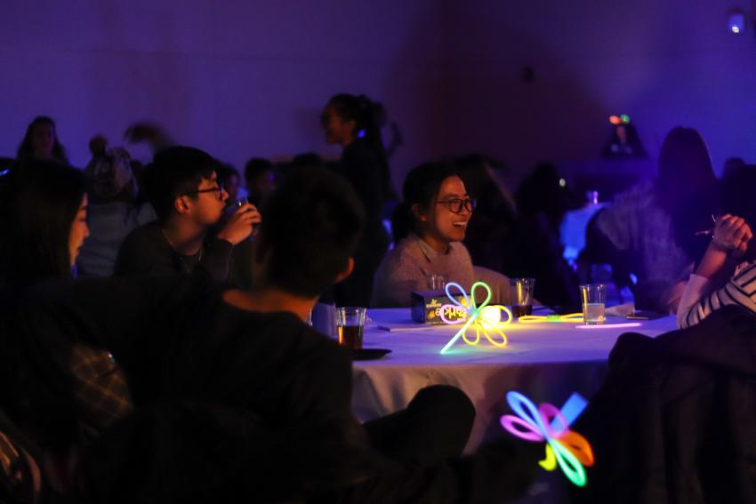 Four students at a round table in the Great Room with glow sticks