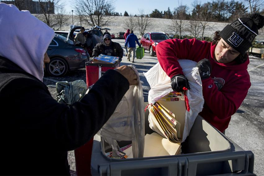 Bryan Gillen '19 helps unload vehicles filled with shreddable materials