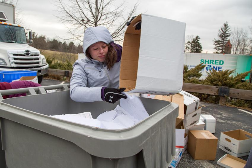 A student pours papers into a large bin from a box so it can be shredded.