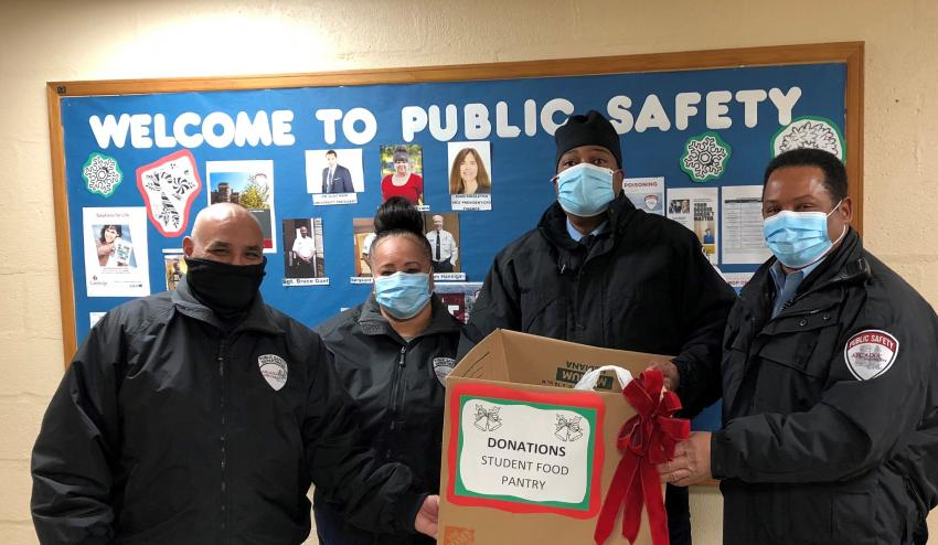 Four public safety officers wearing masks hold box of donations to pantry