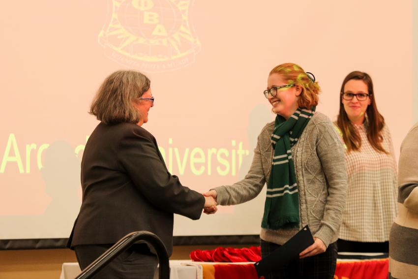 Nancy Rosoff shakes hand of student Caroline Jordan at ceremony