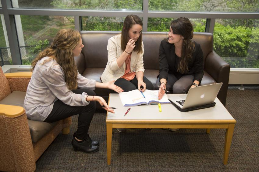 Three female public health students sit looking at a book with laptop open