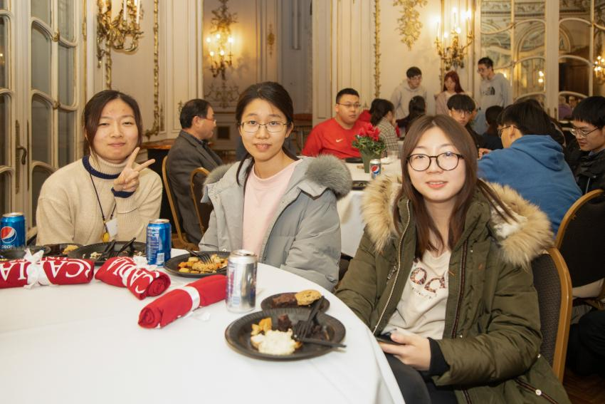 Three Jiangsu students at table with dinner
