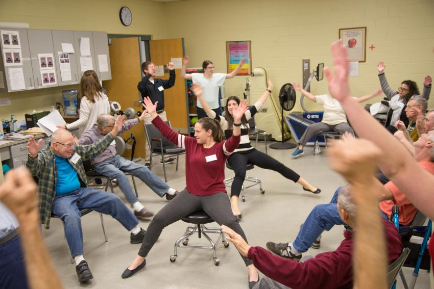 Students show stretches to Stay Fit patients.