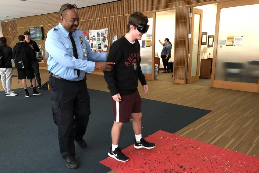 Officer Wayne Forte helping a student wearing the alcohol impairment goggles.