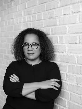 Dr. Erica Armstrong Dunbar leans against a wall in a headshot image.