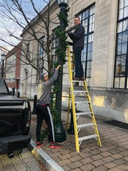 Judge Cerski and a student hang garland on a light post