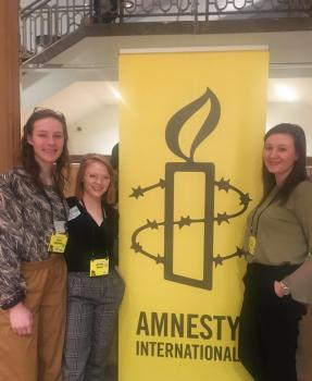 Olivia, Amara and Daisy by an Amnesty International banner