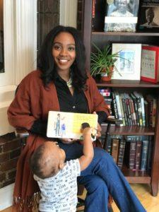 Lisa Browne holding a book and playing with her toddler son