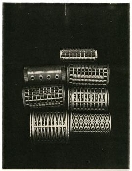 Seven hair curlers xeroxed with black background.