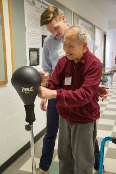Student works with patient at punching bag.