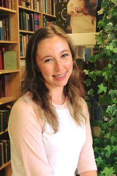 Headshot of Emmalee Gagnon with a bookshelf background.