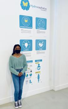 Arcadia University student Mya Brown in front of her designs for HA
