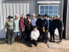 Group shot of 10 members of the team, some wearing cowboy hats